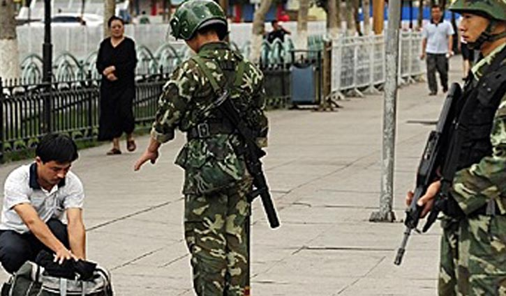 Chinese paramilitary policemen search a man's bag on a street in the Xinjiang region. (File Photo)